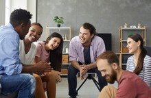 Young Mixed Race People Having Fun And Enjoying Good Time Together. Diverse Group Of Six Happy Millennial Friends Sitting On The Sofa In The Living-room And Laughing At A Funny Joke