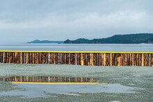 A Breakwater Made Of Wood Logs And Painted Bright Yellow On The Top. There's An Ocean And Mountains Over The Wall. Before The Seawater, There's A Water Puddle With The Fence Reflecting In The Water.