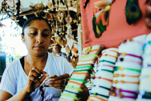 Young Female Craftswoman Concentrating While Preparing Decoration At Shop