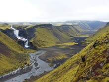 Valley At Eldgjá, Iceland. Green Vegetation, Blue River, And A Waterfall.