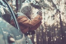 Woman In Warm Jacket Leaning Out Of Car Window Exploring And Photographing Using Dslr Camera Along The Forest. Woman With Curly Hair And Warm Jacket Taking Pictures In The Forest Using Digital Camera