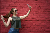 Millennial female blogger shooting influence vlog via cellphone front camera using mobile application at publicity area with copy space area, Caucasian hipster girl in sunglasses taking selfie photos
