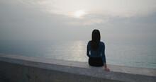 Woman Sit On Seaside And Enjoy Sunset