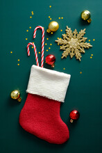 Red Santa Stocking With Candy Canes, Golden Balls, Snowflake On Green Background. Top View.