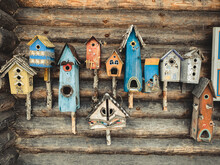 A Large Number Of Colorful Birdhouses On The Wall Of The Log Cabin