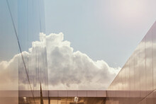 Clouds In Sky Reflected In Glass Building Surface. Photo Tinted With Orange Blue Gradient Color.