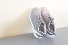 Pair Of Female Sport Shoes Standing On Gray Surface Next To Yellow Wall. Photo With Copy Blank Space.