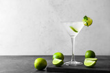 Glass of tasty margarita cocktail and limes on light background