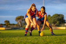 Two Aussie Rules Football Players Going For The Ball