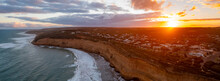 Panoramic Aerial View Of Waves Rolling In On A Rugged Coastline At Sunset