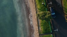 Birds Eye Aerial Footage Over A New Zealand Shore With Blue Ocean Waters. Off Centre To The Shore