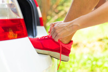 Women's Hands In The Forest Near The Car Against The Background Of Green Trees On A Bright Summer Sunny Day Tie The Laces Of Sneakers. Selective Focus