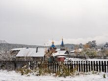 Russian Rural Village Chemal In The Snow. A Church With A Blue Roof And Golden Domes Against The Backdrop Of The Altai Mountains Can Be Seen Behind A Wooden Fence. Chemal, Altai Republic, Russia.