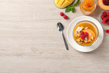 Delicious Mango Jelly With Fresh Raspberries And Almond Flakes On Light Wooden Table, Flat Lay. Space For Text