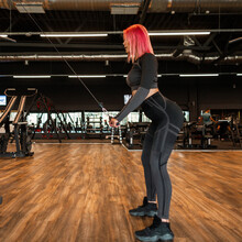 Young Beautiful Sportswoman In Black Fashionable Sportswear With Shoes Trains And Pumps Muscles On The Machine In The Gym, Side View
