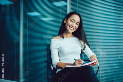 Carta da parati Portrait of Asian female employee with textbook creating business management and