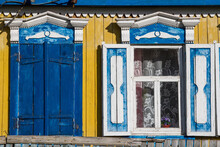 Yellow Wall Of The Wooden House With Beautiful Window Frames.