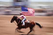 Cowgirl Rides In Rodeo With American Flag. Motion Blur Galisteo, New Mexico, United States.