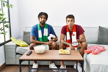Young Hispanic Brothers Football Hooligans Holding Ball And Megaphone Thinking Attitude And Sober Expression Looking Self Confident