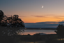 Waxing Crescent Moon Over The Sea At Sandwich Bay During The Golden Hour Sunset.