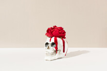 Skull With Blood Red Flower Rose On Pastel Background. Minimial Love Halloween Or Santa Muerte Concept.