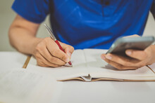 Closeup Shot Of A Male Student Taking Notes Reading Off A Smartphone