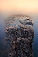 Abstract Cliff At The Water's Edge With Smooth Water In Sunset Light