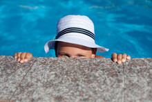 Child In White Panama Hat Plays In Pool. Happy Charming Girl In White Straw Hat Decorated With Ribbon Looks Out From Behind Granite Side Of Pool, Holds Her Hands It And Looks At Camera.