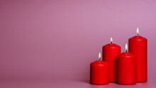 Four Burning Candles On Pastel Magenta Background