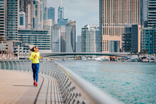Happy Woman Wearing Headphones And Sunglasses Trains And Does Running And Fitness On The Sidewalk Of The Embankment In The Dubai Marina Area