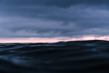 Cloudy Sunset Over The Dark Ocean With A Bright Stripe Over The Horizon