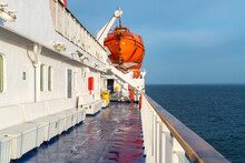 Orange Life Boat Hanging On A Crane On A Deck Of Sailing Ocean Ship With Ocean Horizon In The Back And Wooden Railing In Front