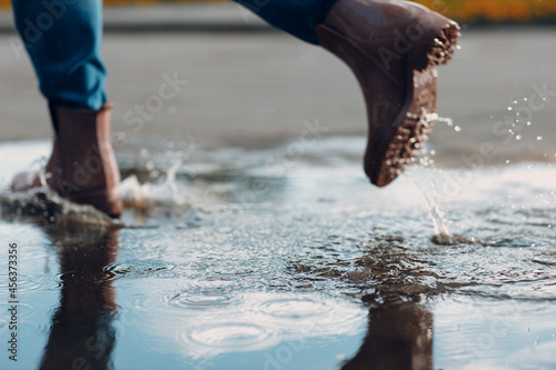 Stampa su Tela Woman wearing rain rubber boots walking running and jumping into puddle with water splash and drops in autumn rain season