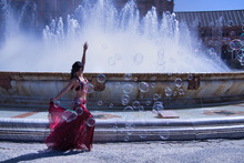 Middle-aged Hispanic Woman, Wearing A Red Dress With Rhinestones, For Belly Dancing, Dancing Surrounded By Soap Bubbles In Front Of A Water Fountain. Belly Dance Concept.