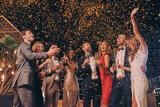 Group of beautiful people in formalwear having fun together with confetti flying all around