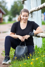 Carefree Woman Walking In Summer Park, Sitting Close To Fence With Black Leather Dag