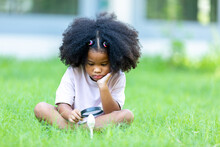 African Girl With Afro Hair Sitting Watching Mushrooms Studying Nature Concept Of Learning The Natural Environment.