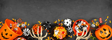 Halloween Trick Or Treat Bottom Border With Jack O Lantern Pails And Mixed Candy. Top View On A Black Banner Background With Copy Space.
