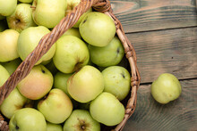 Ripe Freshly Picked Apples In A Basket On A Wooden Background.