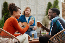 Side View Portrait Of Two African-American Young People Clinking Glasses While Enjoying Outdoor Party With Friends At Rooftop
