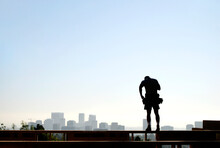 Carpenter Standing On The Top Of A Wood Framed Wall With A View Of The City