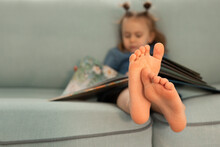 Child Reading Book On Sofa, Children Feet Close Up. Education Conception.Knowledge, Education, Fairy Tales. Kid Sleep And Tired To Read Open Book.Copy Space,place For Text