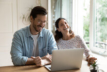 Cheerful Couple Laughing Sit At Desk In Front Of Laptop, Enjoy Funny Humorous Internet Content Videos, Have Fun Use Online Website Making Easy Delivery Order, Buying On Ecommerce Services Feel Happy