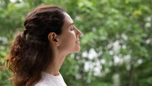 Profile Close Up Face Serene Woman Standing Outdoor Closed Eyes Breath Fresh Air Feels Motivated Enjoy New Day, Green Trees On Background. No Stress, Filling With Positive Emotions, Meditation Concept
