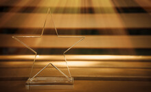The Prize For The First Place Is In The Form Of A Glass Star On A Brown Background, A Ray Of Sun Shines From The Side. A Clean Place For The Text