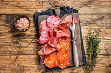 Cured Meat Platter Served As Traditional Spanish Tapas. Salami, Jamon, Choriso Sausages On A Wooden Board. Wooden Background. Top View