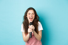 Excited Pretty Girl Singing Karaoke, Holding Microphone And Smiling Happy, Standing Over Blue Background