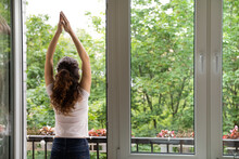 Rear Back View Awakened Woman Standing Alone In Summer Terrace Raise Hands Up Perform Stretching Exercises, Breath Fresh Air, Enjoy Admires Scenery Nature Greets New Day. Wake Up, Good Morning Concept