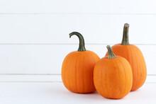 Three Pumpkins On White Wood