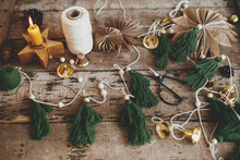 Stylish Christmas Fir Trees Garland, Thread, Bells, Paper Stars, Ornaments, Candle, Scissors On Rustic Wooden Background. Making Festive Eco Garland, Atmospheric Holiday Decor. Merry Christmas